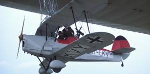 El Stampe et Vertongen  V.4 a punto de liberarse del dirigible LZ-138. Se trataba de un biplano de entrenamiento y turismo belga, que voló por primera vez en 1933. La ametralladora trasera es puro atrezzo. Verdaderamente los dirigibles alemanes nunca llevaron aviones adosados (Fuente: impdb.org)