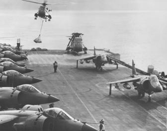Gran carga de trabajo en la cubierta de uno de los portaaviones de la Navy durante las Malvinas. Podemos ver dos helicópteros Sea King, y varios Harrier GR.3 y Sea Harrier FRS.1, distinguibles por su morro más afilado. (Fuente: Grand Logistics)